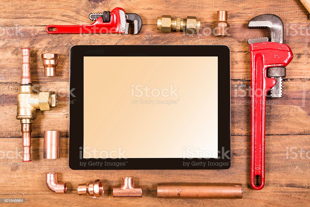 Construction, plumber's wreches, copper pipes surround a digital tablet. stock photo