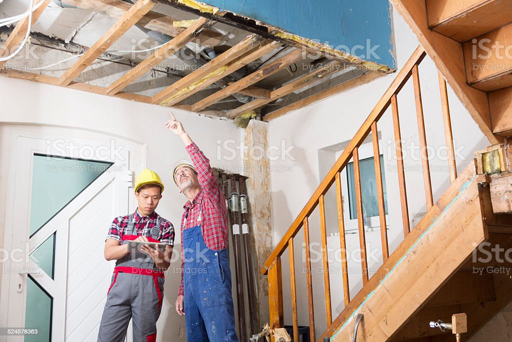 construction reconstruction old house worker tablet pc stock photo