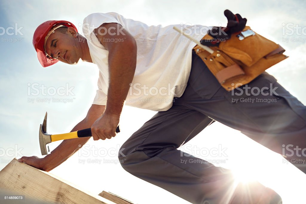Construction roofer nailing wood board with hammer stock photo