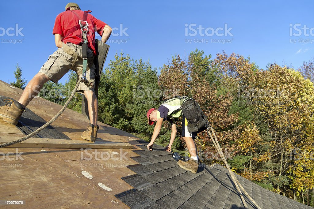 Construction Roofers wearing proper Safety Equipment - Stock Image stock photo