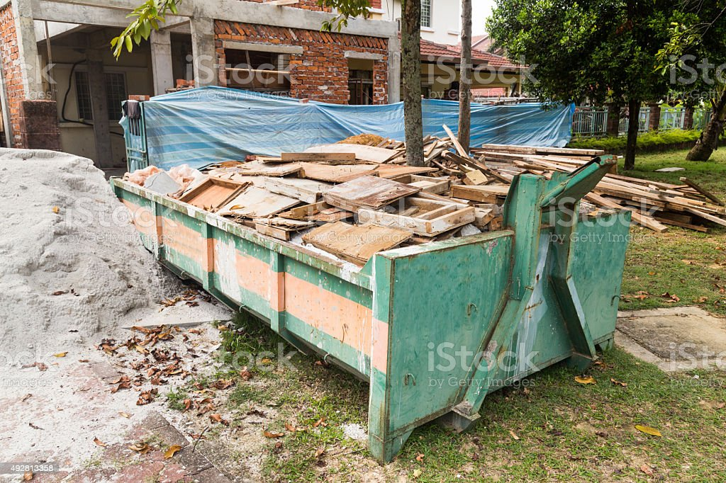 Construction rubbish bin with loads at construction site stock photo