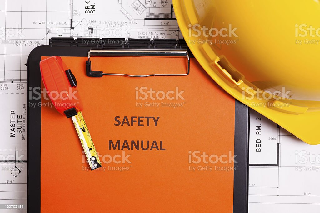 Construction:  Safety manual and workman's tools on floorplans. stock photo