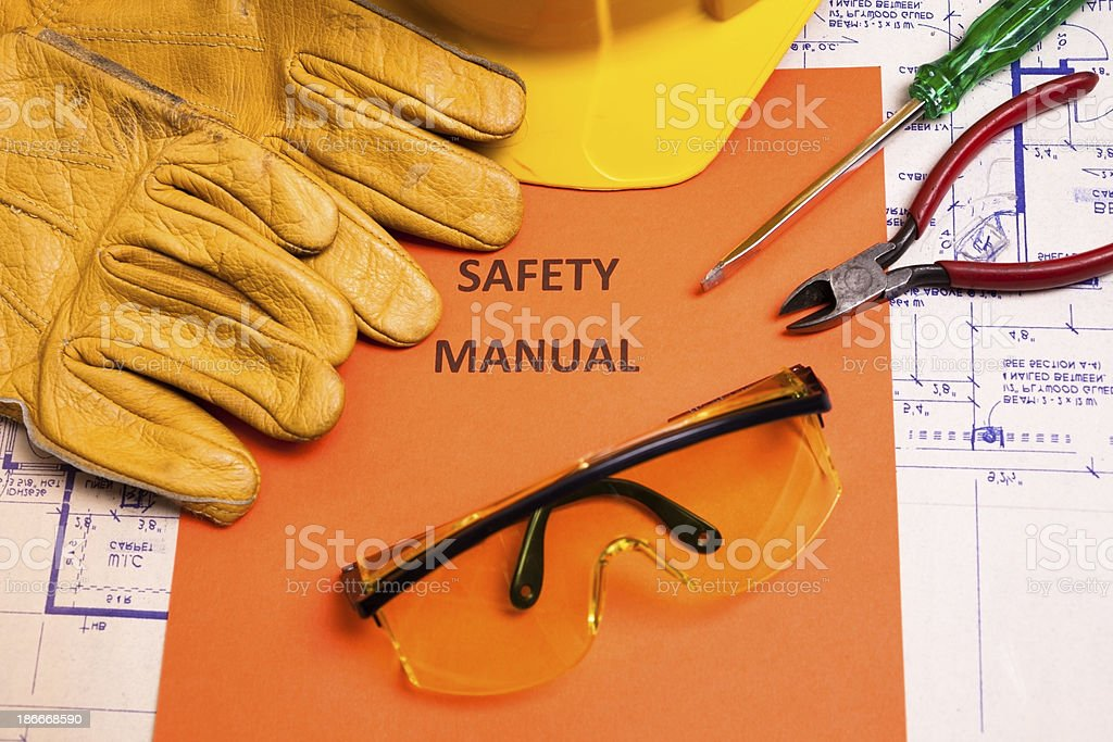 Construction:  Safety manual and workman's tools on houseplans. stock photo