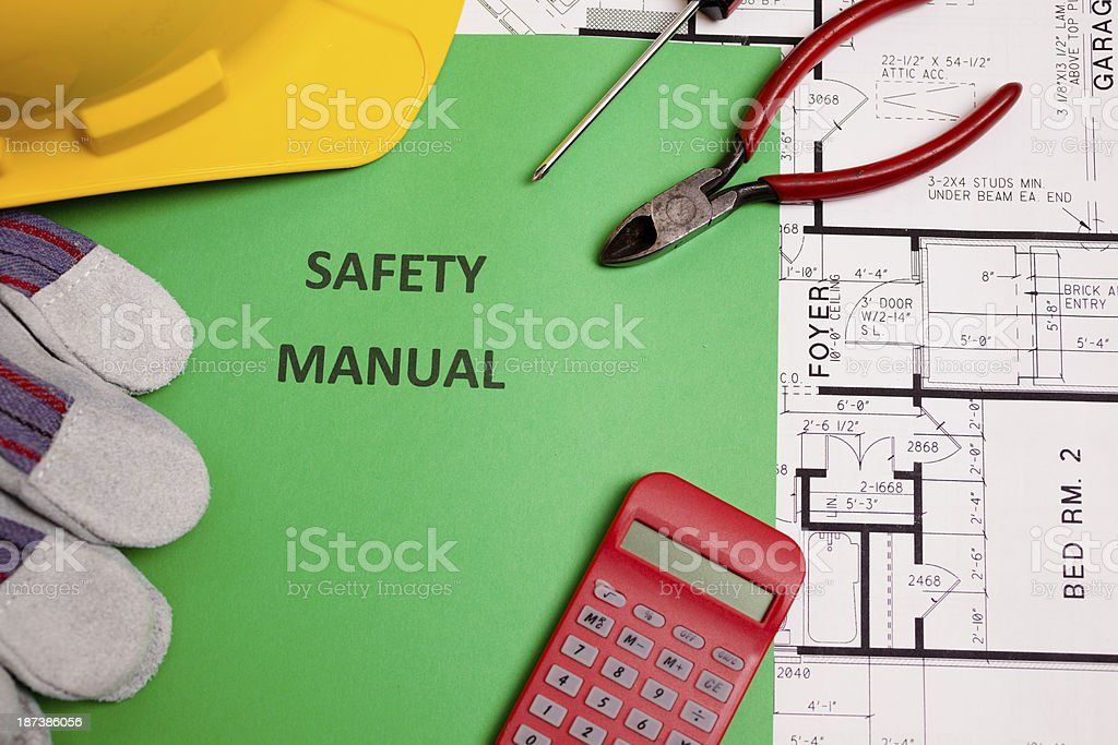 Construction:  Safety manual and workman's tools on houseplans. royalty-free stock photo