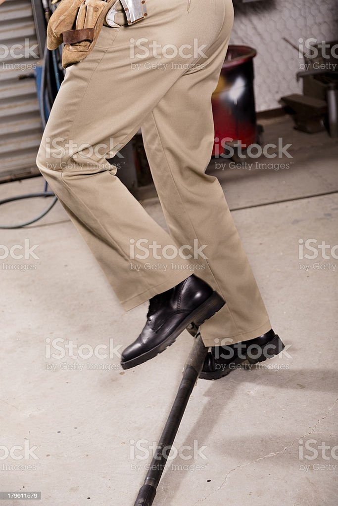 Construction Safety:  Worker falling over an axle left on floor. stock photo