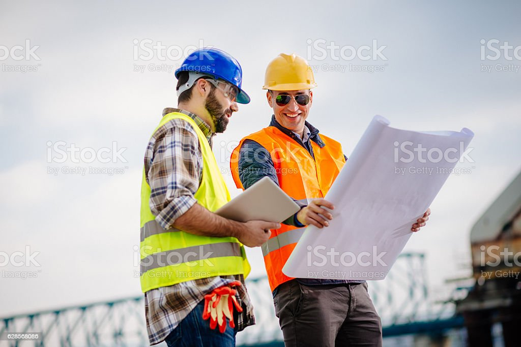 Construction site and construction workers with blueprint stock photo