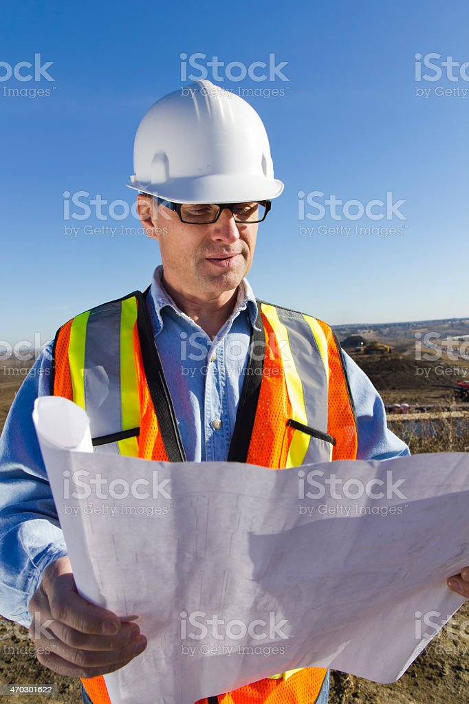 Construction Site Engineer and Blueprints stock photo