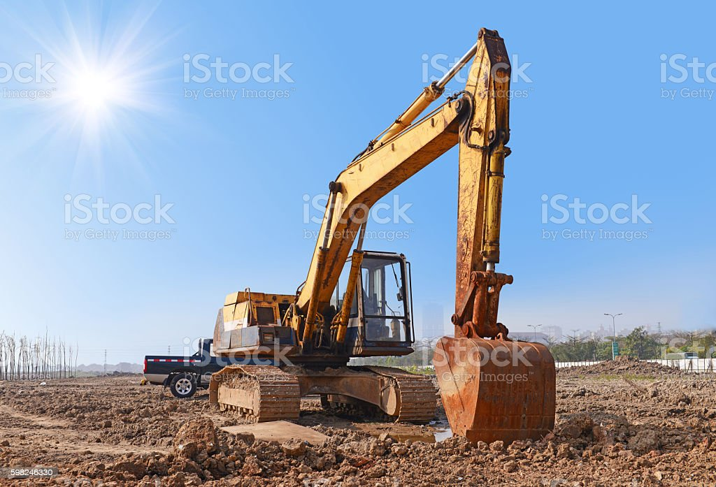 Construction site excavator with blue sky under the sun. stock photo