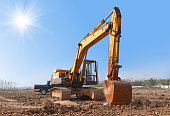 Construction site excavator with blue sky under the sun.