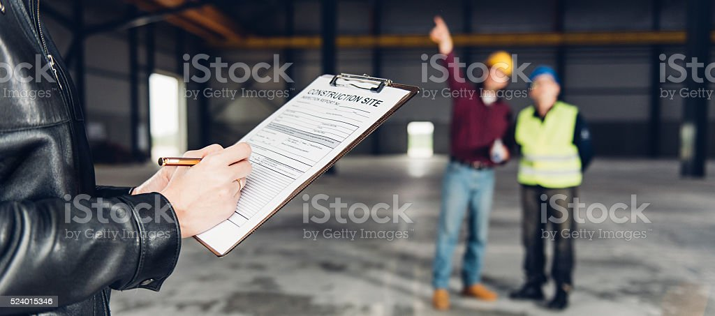 Construction Site Inspector making report stock photo