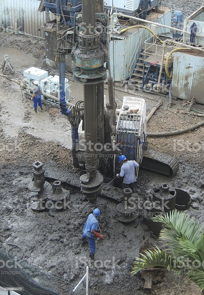Construction site: maintaining a hole drilling machine stock photo