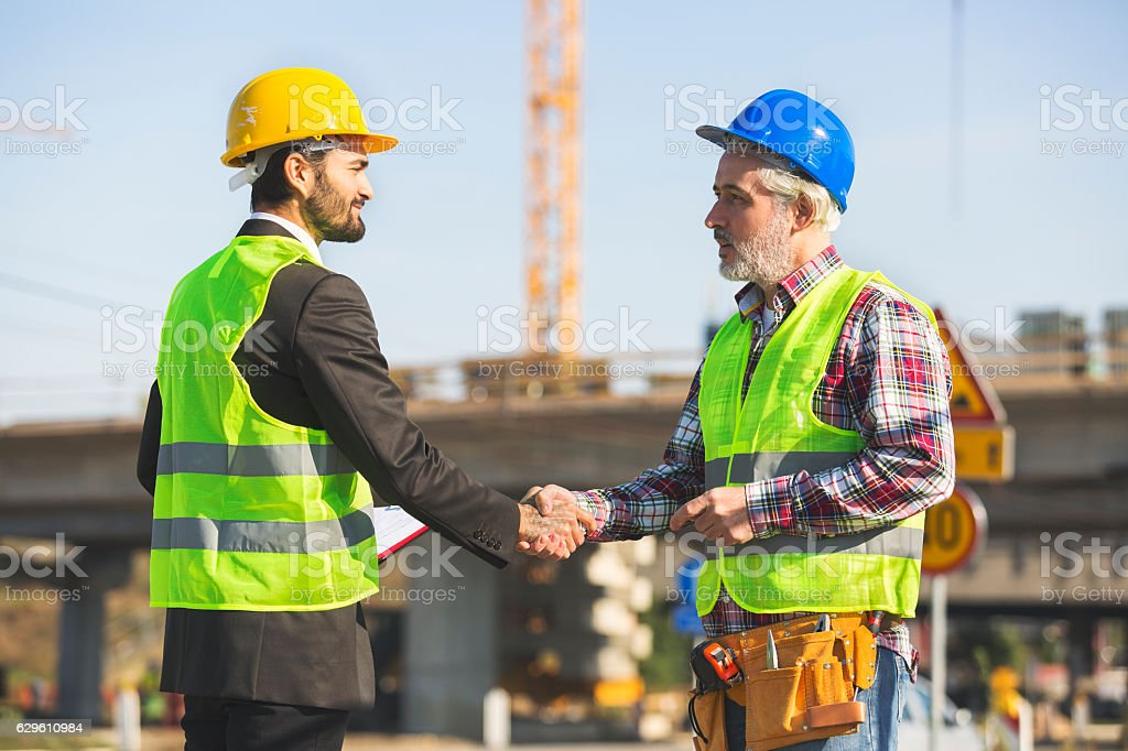 Construction site manager and mature employee shaking hands royalty-free stock photo