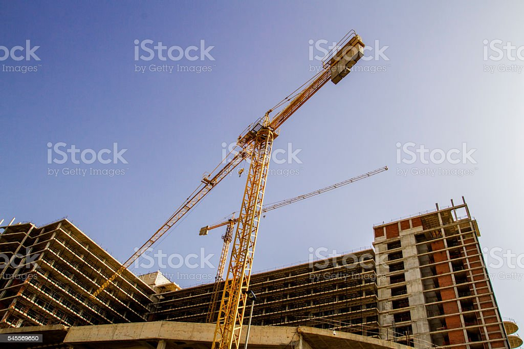 Construction site. New building. Yellow tower crane against blue sky. stock photo