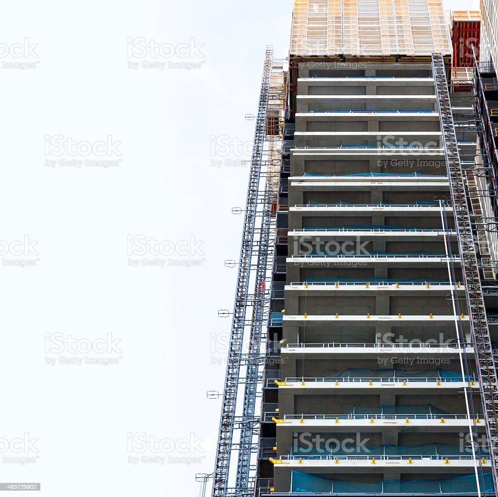 Construction site of skyscraper with tower crane and construction elevator stock photo