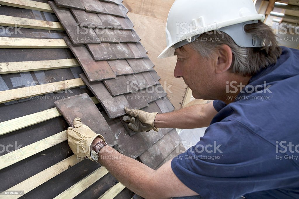 Construction Site Roofer Laying Roof Tiles stock photo