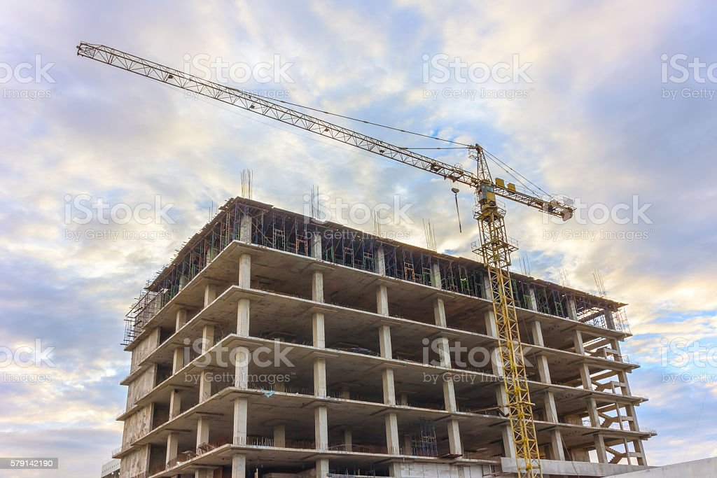 Construction site with crane and building at sky sunset. stock photo