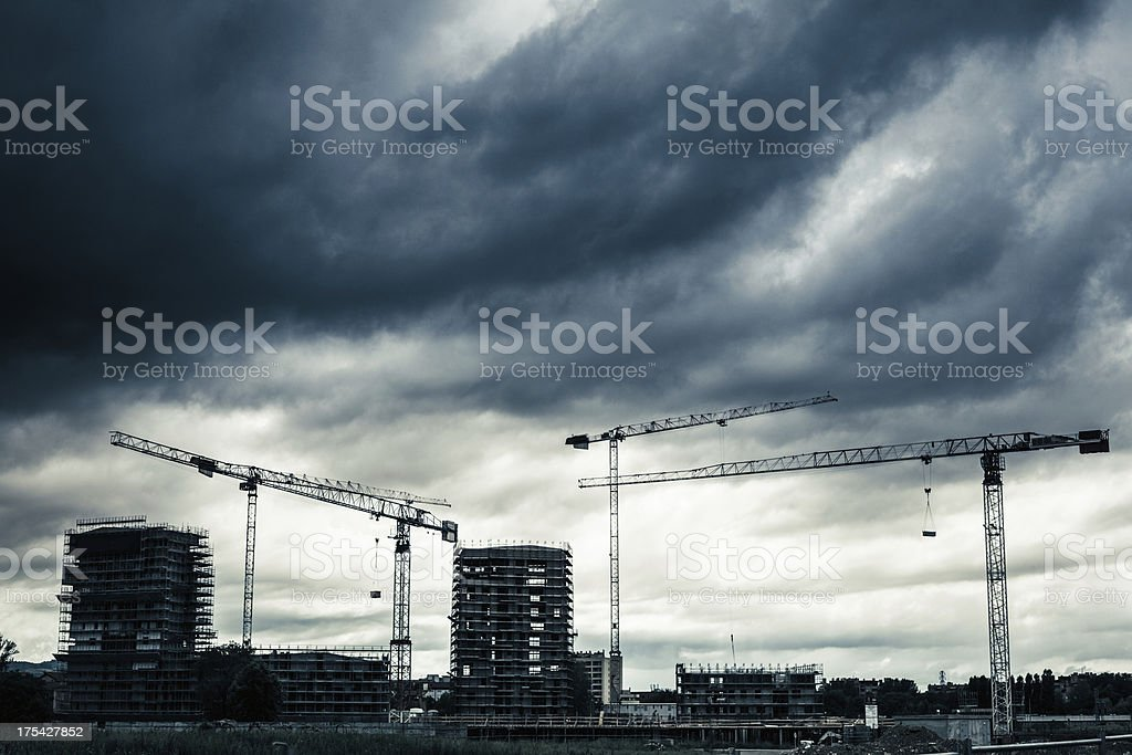 Construction Site with Cranes and Cloudy Sky stock photo