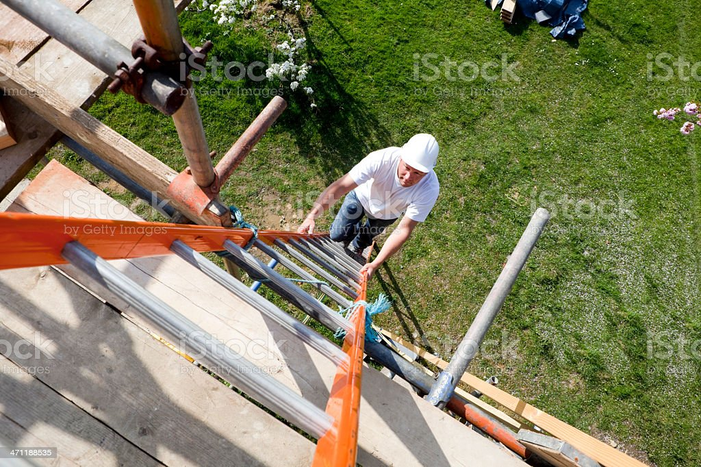 A construction site worker climbing a ladder royalty-free stock photo