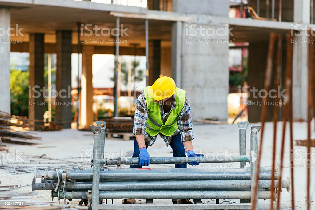 Construction site worker lifting steel bars on construction platform stock photo
