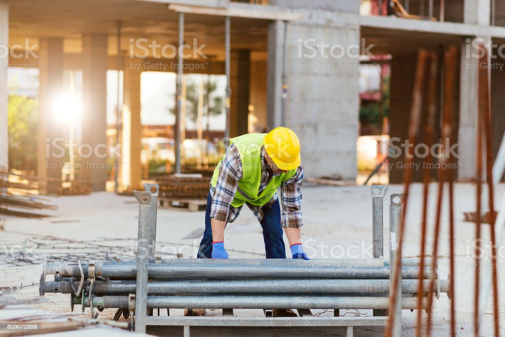 Construction site worker lifting steel bars stock photo