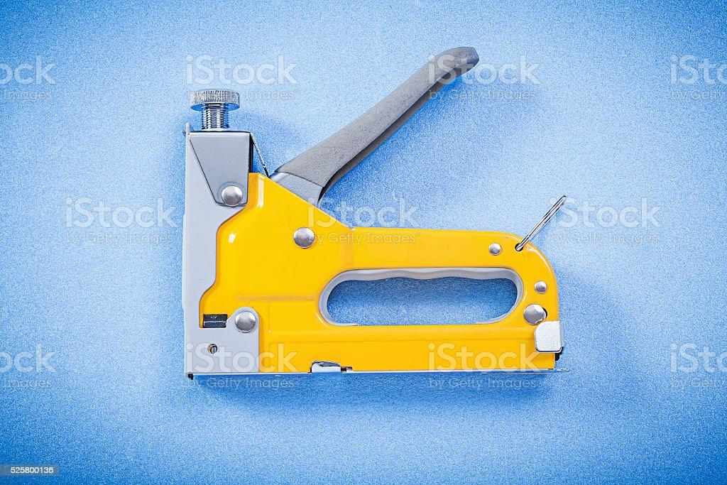 Construction stapler on blue background horizontal view stock photo