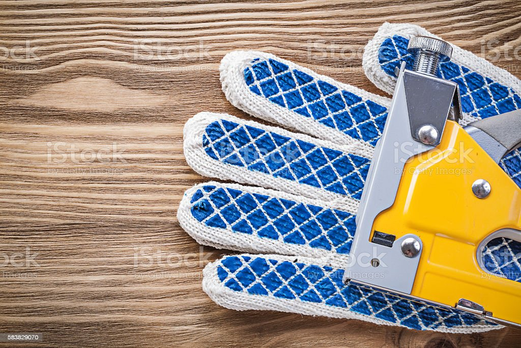 Construction stapler working gloves on wooden board directly abo stock photo