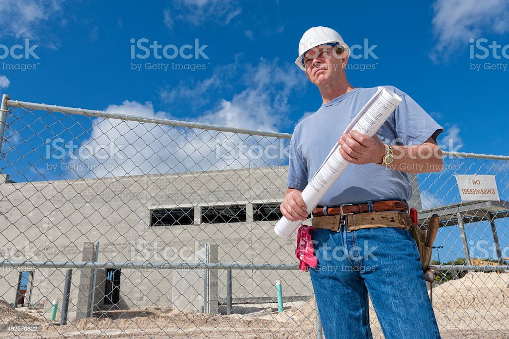 Construction Superintendent Holding Set of Plans on Construction Site stock photo
