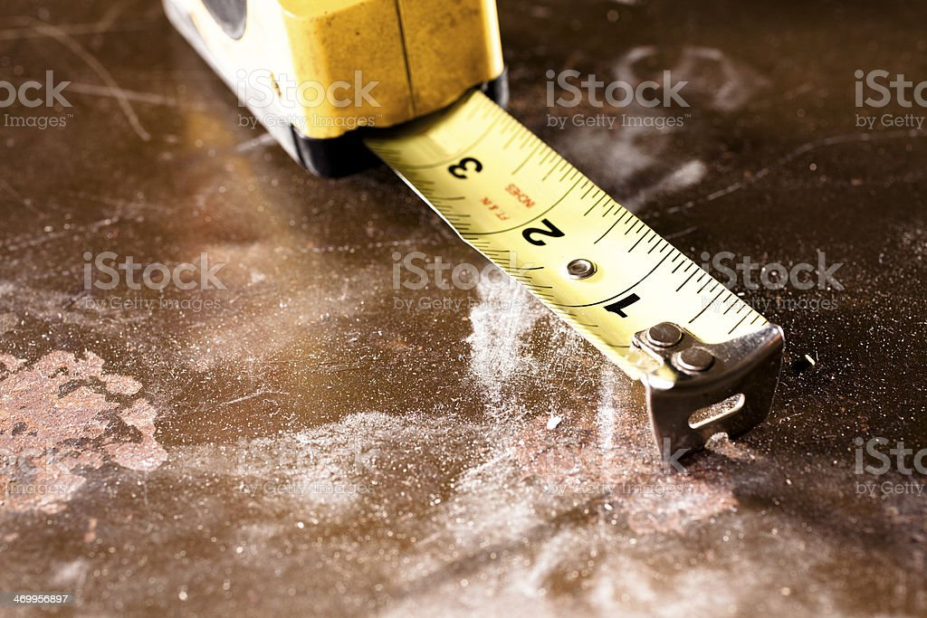 Construction: Tape measure on workshop table top. Grunge. stock photo