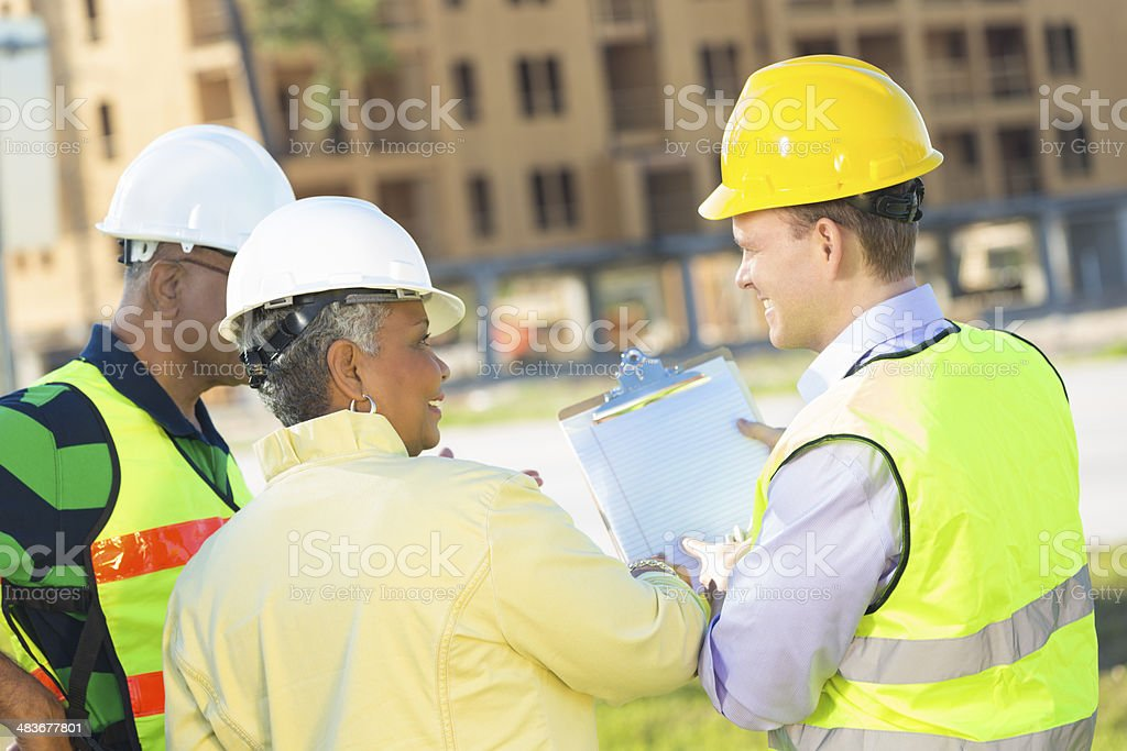 Construction team checking checklist at work site royalty-free stock photo