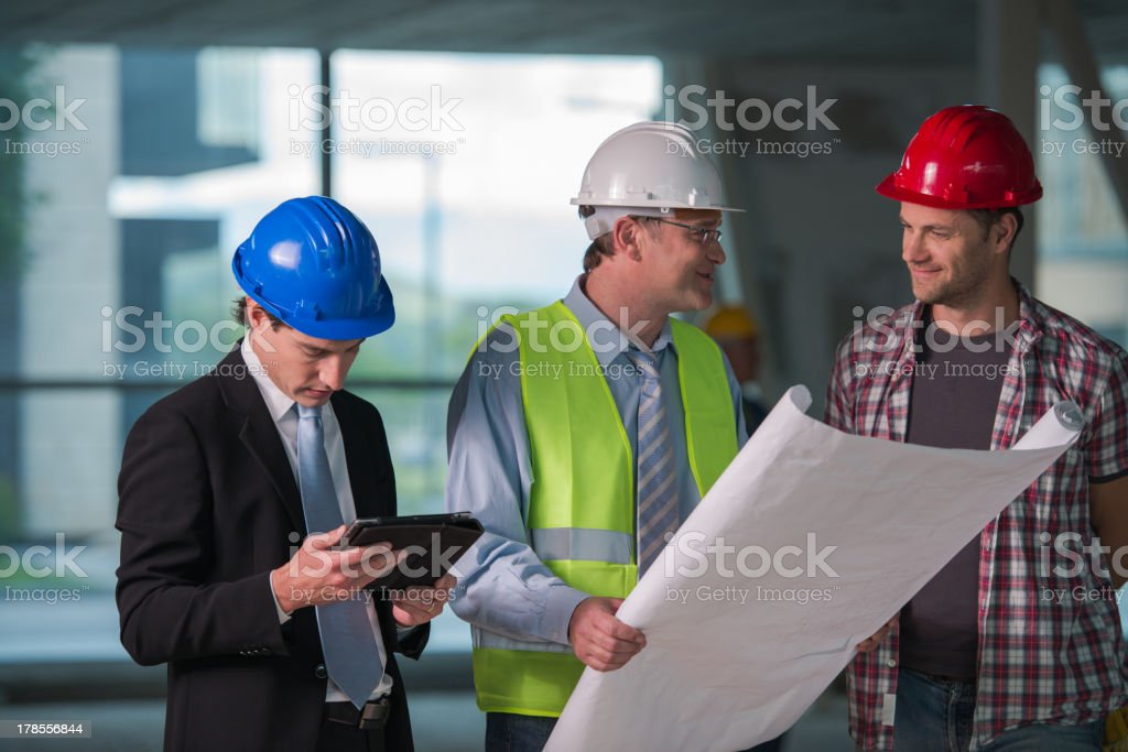 Construction team reviewing blueprints together royalty-free stock photo