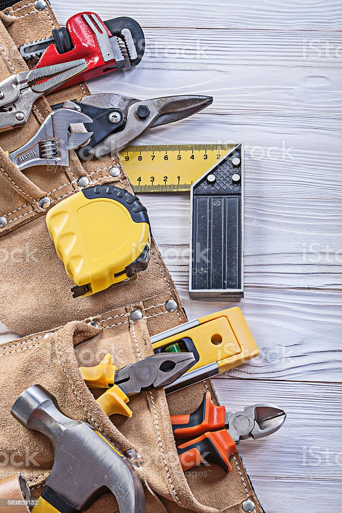 Construction tooling in tool belt on wooden board maintenance co stock photo