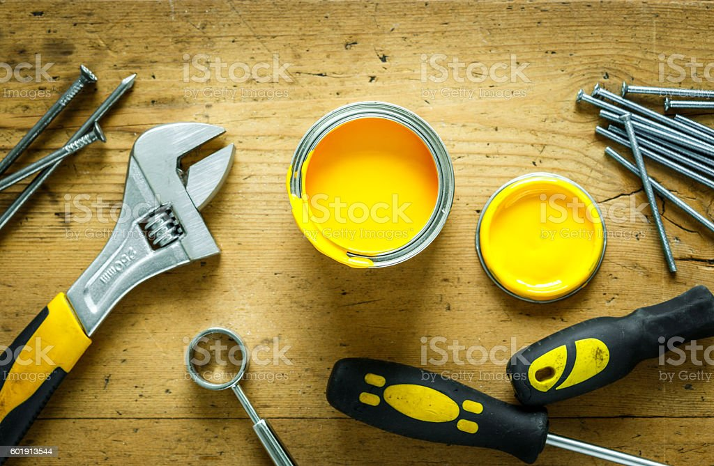 construction tools on a wooden table with yellow paint stock photo