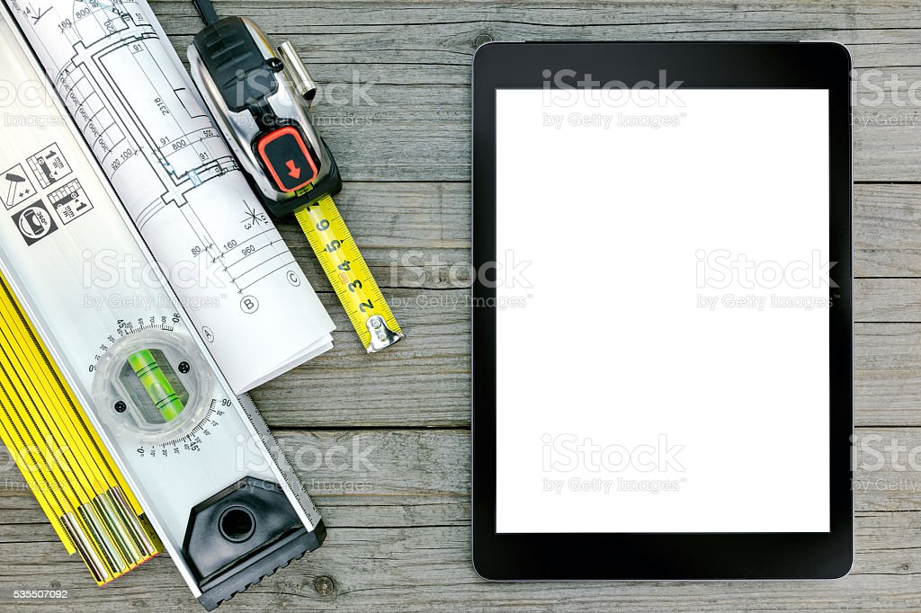 construction tools with blueprint and digital tablet over gray wood stock photo