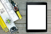 construction tools with blueprint and digital tablet over gray wood