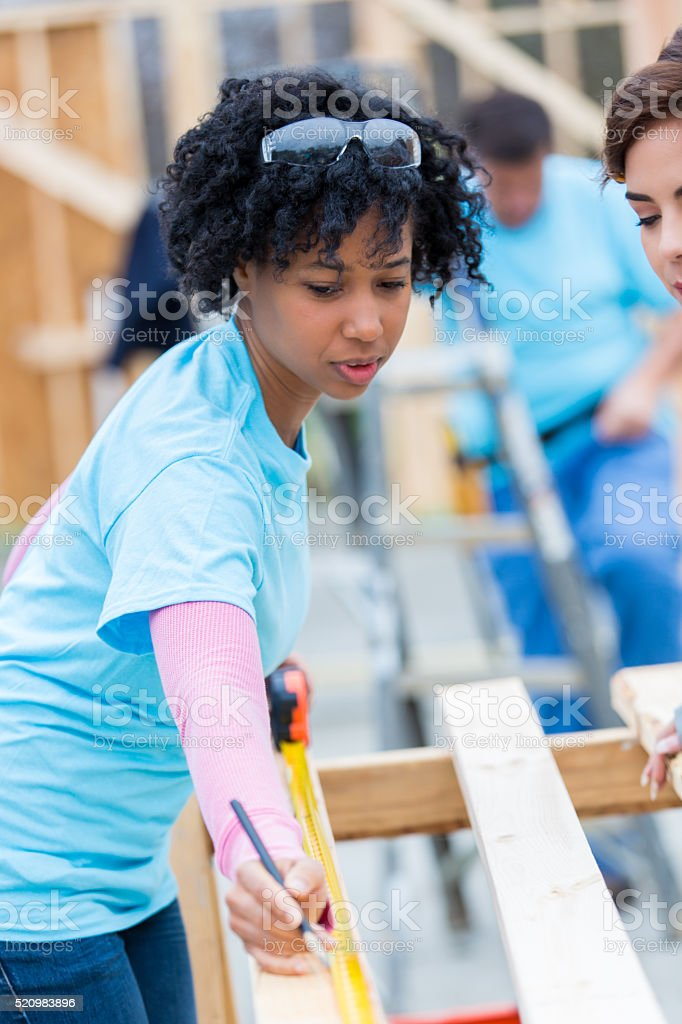 Construction volunteer measures board stock photo