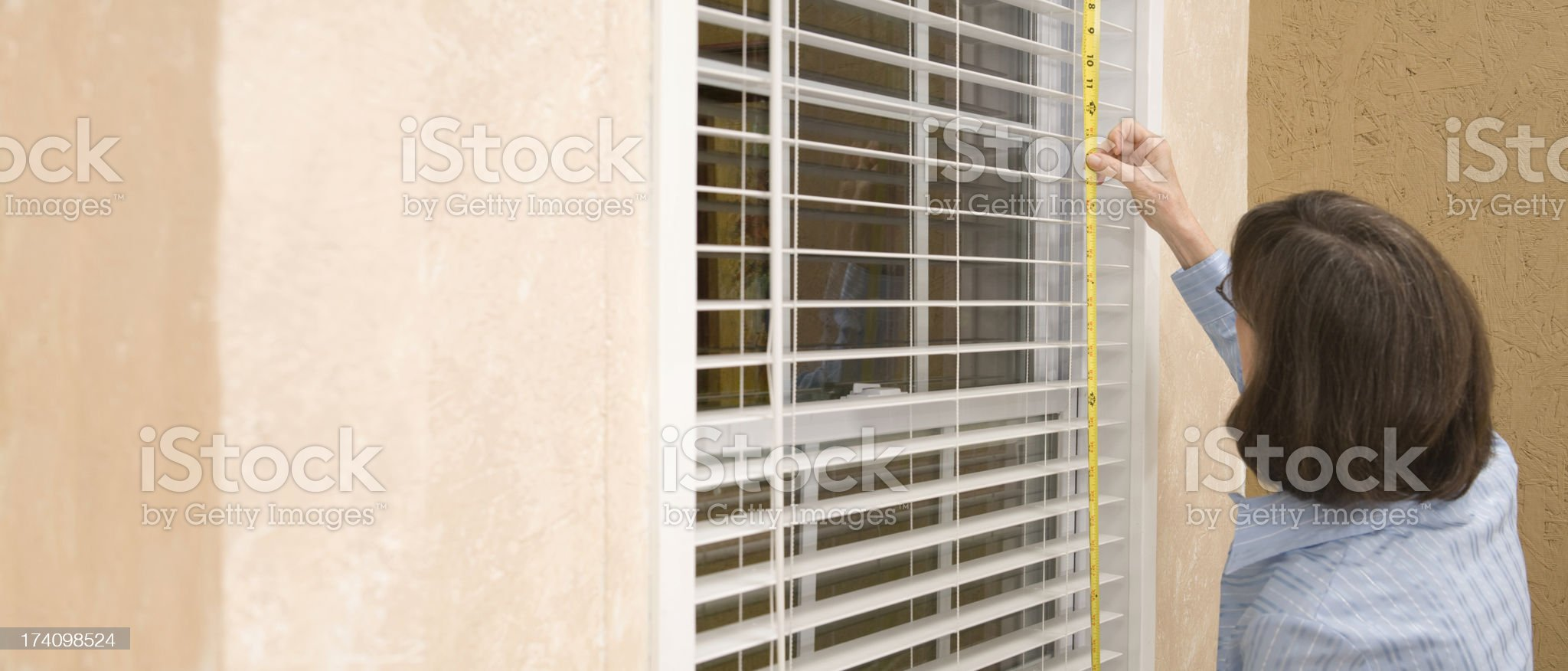 Construction: Woman measures windows for new window coverings. royalty-free stock photo