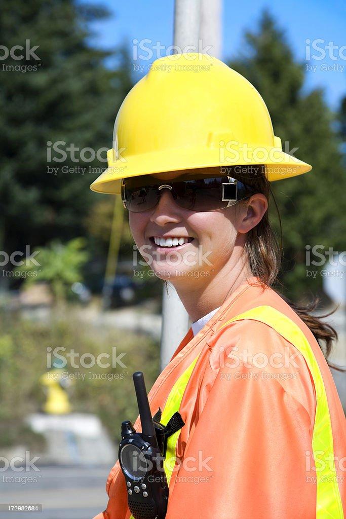 Construction Woman on the job site orange safety gear helmet stock photo