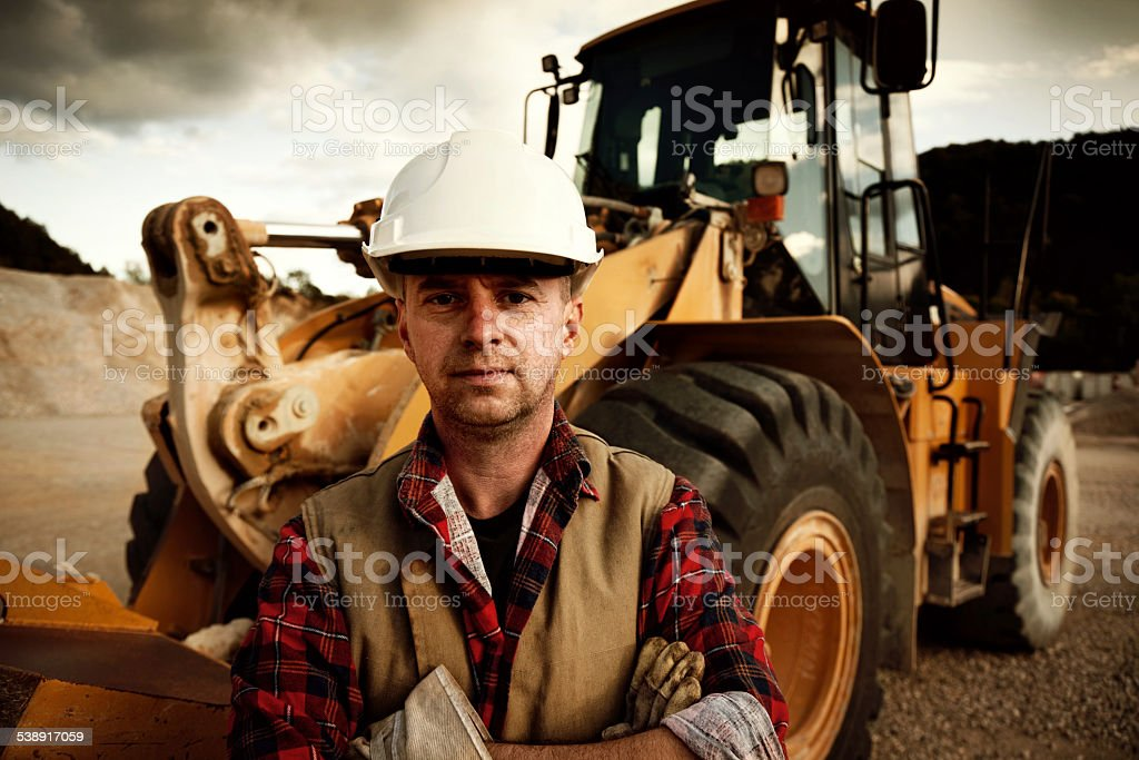 construction worker against earth mover in background stock photo