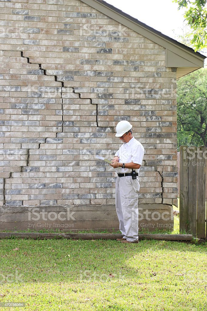 Construction worker analysing house foundation damage stock photo