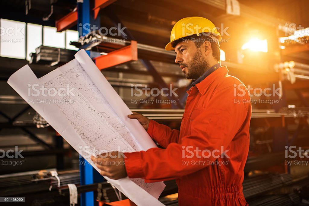 Construction worker analyzing blueprints in industrial building. stock photo
