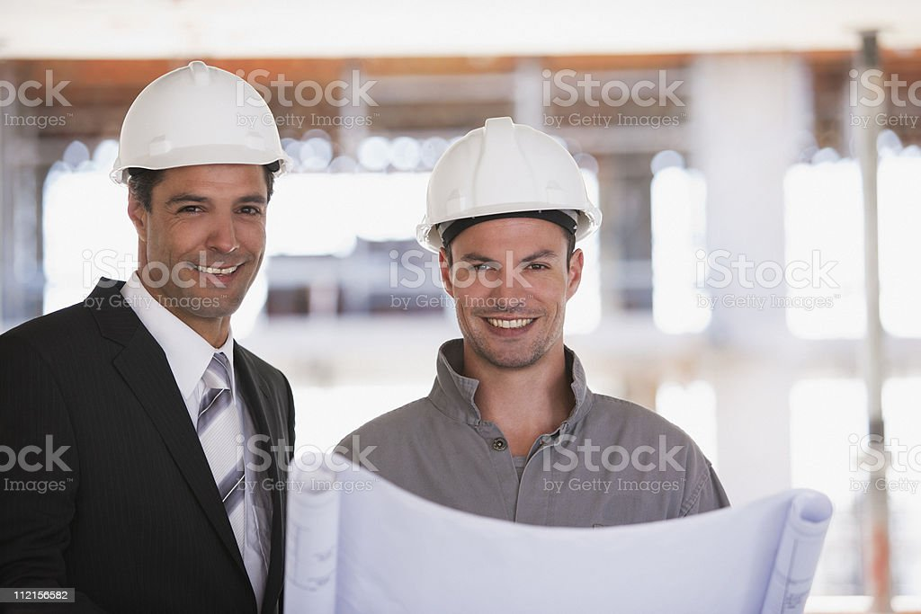 Construction worker and businessman looking at blueprints on construction site royalty-free stock photo