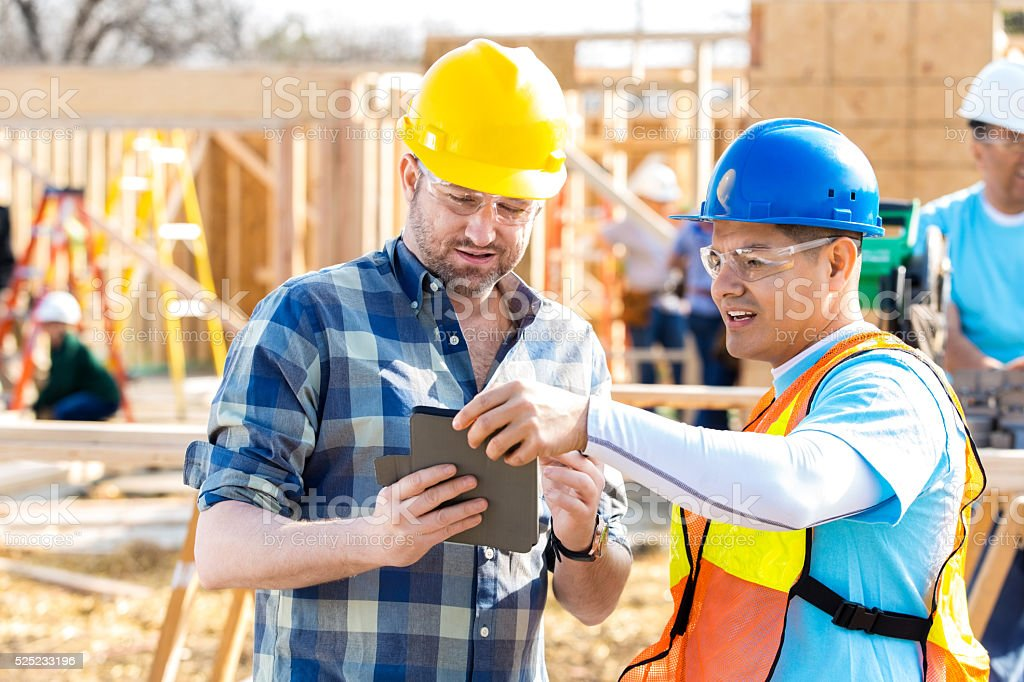 Construction worker and foreman review building plans stock photo