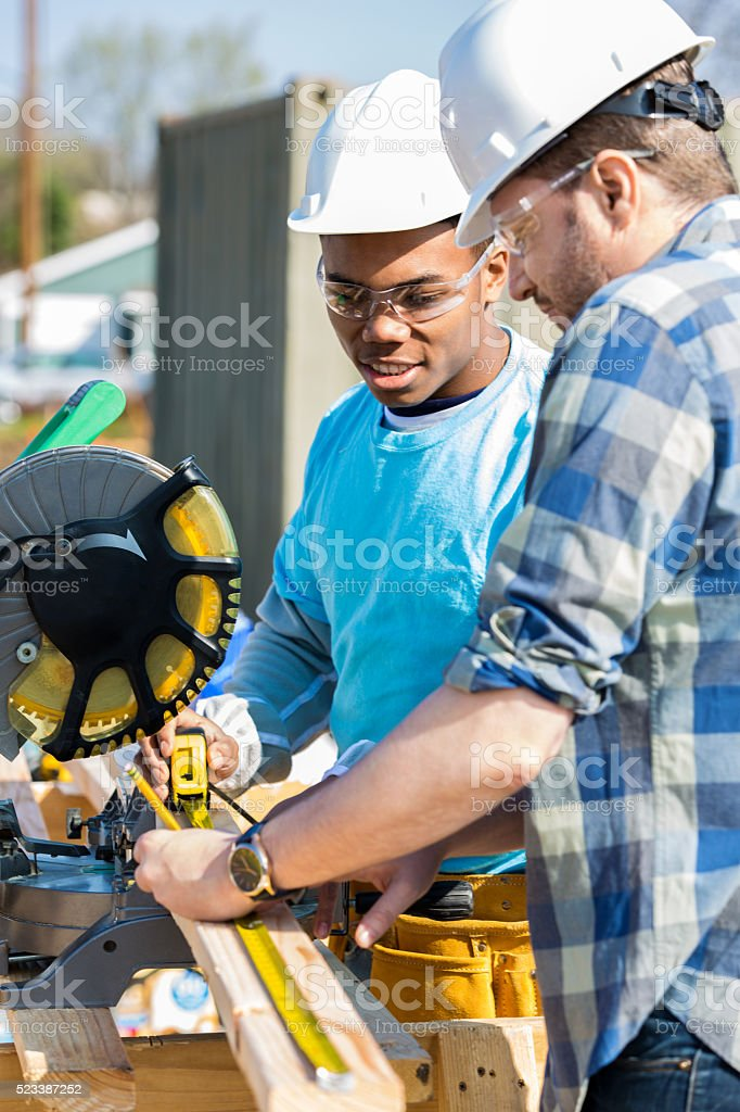 Construction worker and trainee use saw to work site stock photo