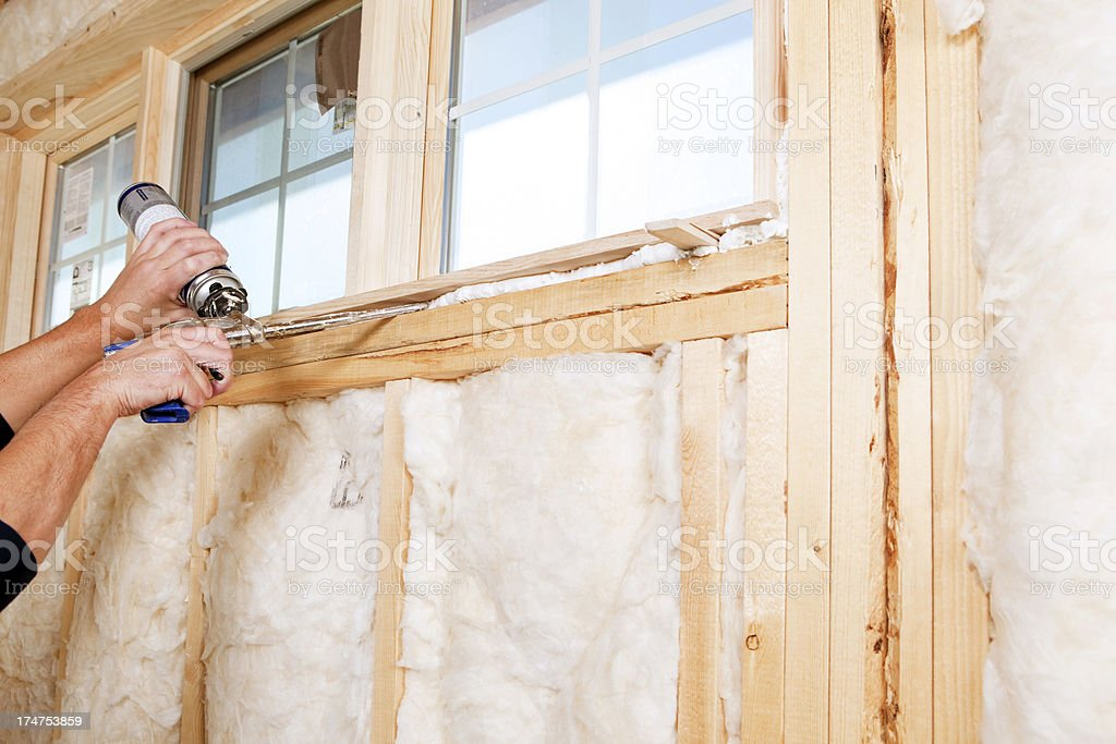 Construction Worker Applying Expandable Foam Insulation to Windo stock photo
