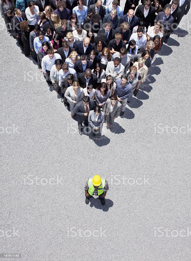 Construction worker at apex of pyramid formed by business people stock photo