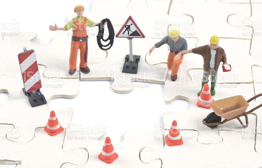 construction worker build on last puzzle piece stock photo