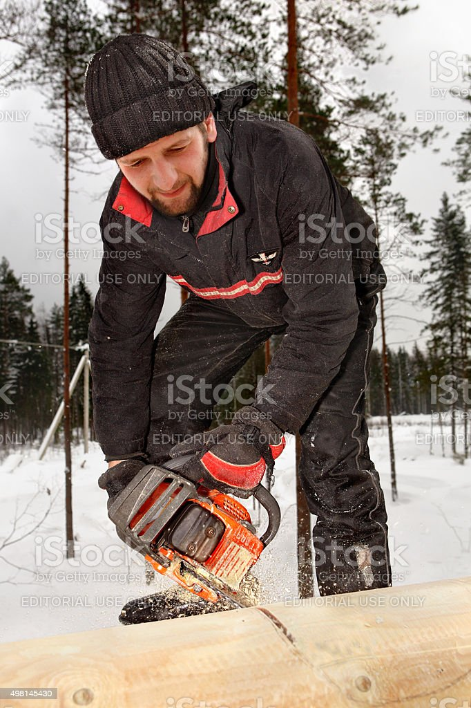 Construction worker builds wooden blockhouse from logs, using chainsaw. stock photo