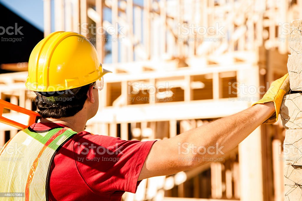 Construction worker busy working at job site. Framed building. Materials. stock photo