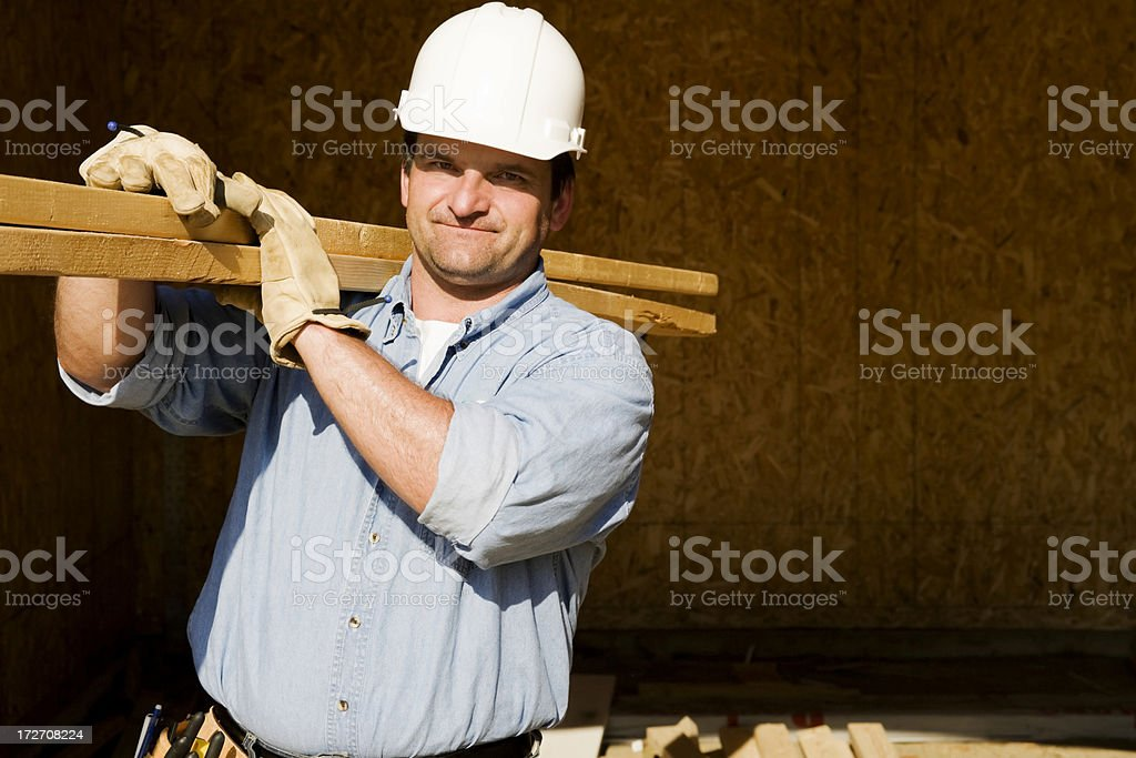 Construction Worker Carrying 2x4s royalty-free stock photo