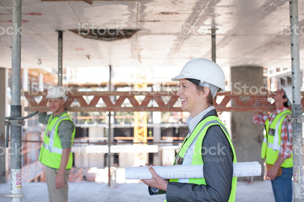 Construction worker carrying blueprints on construction site stock photo